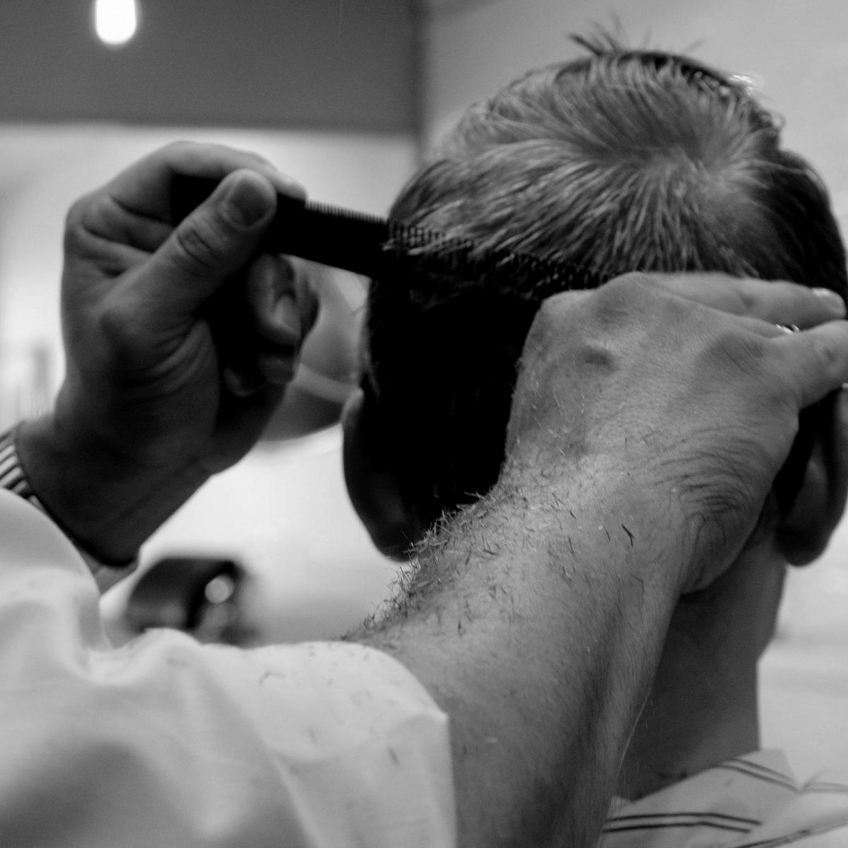 Frisör som klipper en kund